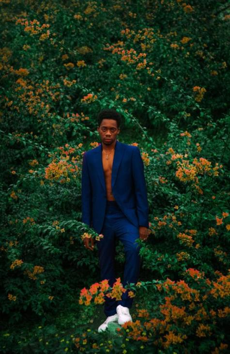 Man in a blue suit posing in the middle of a garden