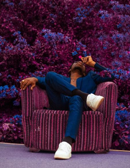 Man in blue sit with holding a pink flower, sitting on a purple stripped chair looking upwards. The background is purple and blue flowers