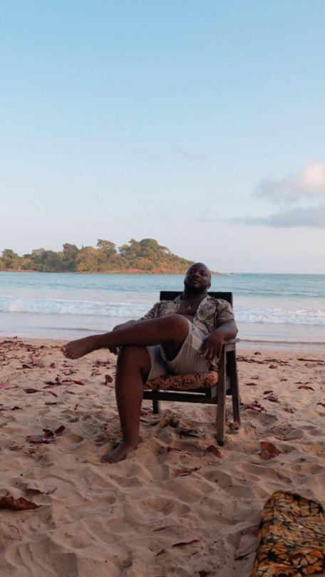 Man with unbuttoned shirt sitting on a chair on the beach