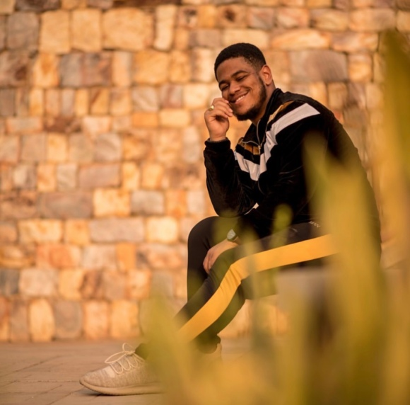 Light skinned man in a tracksuit sitting in front of a stone wall and posing for a picture