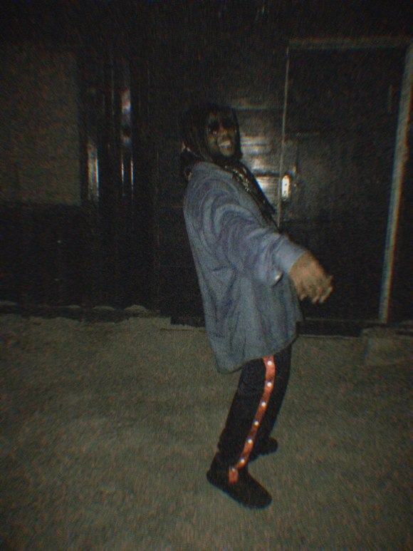 Blurred photo of a man smiling at the camera with his right hand outsretched and a scarf tied around his dead